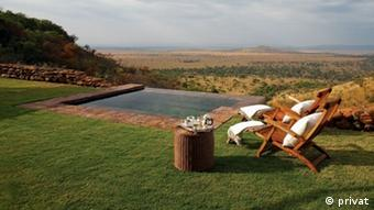 Two reclining chairs by a pool – with a view of the Serengeti.