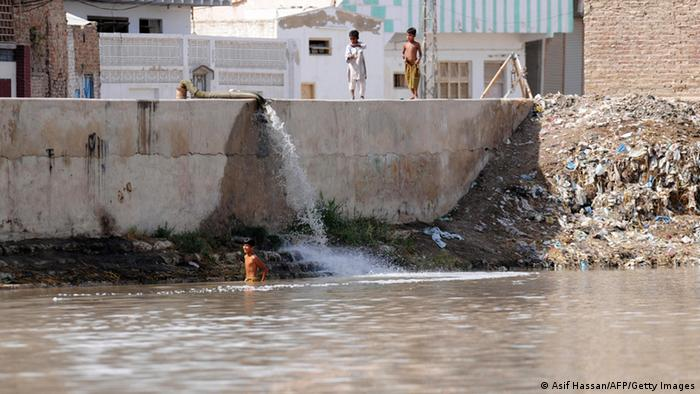 Children bathing near in Indus as sewage flows in