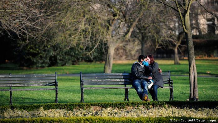 In einem Park küsst sich auf einer Bank ein Liebespaar.