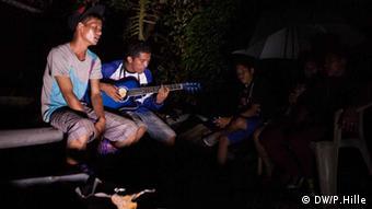 Die Insel Leyte wurde besonders schwer getroffen vom Taifun Haiyan. Fast eine Woche nach dem Sturm sind dort noch immer tausende Menschen ohne Strom und Trinkwasser. An einigen Orten gibt es jedoch Hoffnungszeichen. Mit der Gitarre gegen die Dunkelheit Teking Etang Ormoc. Foto: Peter Hille DW 14.11.2013