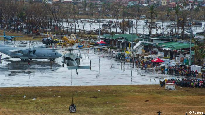 A U.S. Navy MH-60S helicopter drops supplies at Tacloban Air Base, REUTERS/Specialist 3rd Class Ricardo R. Guzman/US Navy/Handout (