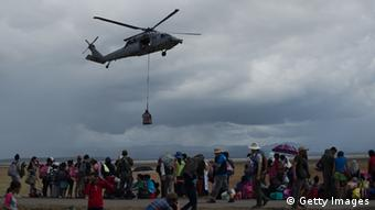 A US navy helicopter delivers relief supplies at Tacloban Airport (Photo: NICOLAS ASFOURI/AFP/Getty Images)