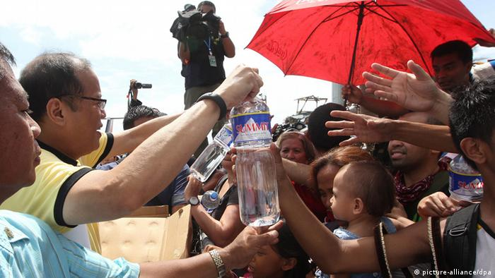 President Benigno Aquino gives out water to families displaced by Typhoon Haiyan during his visit to Tacloban City (Photo: EPA/RYAN LIM/ MALACANANG PHOTO BUREAU HANDOUT)