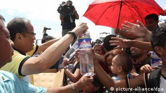 epa03943724 A picture made available by the Malacanang Photo Bureau shows President Benigno S. Aquino III (2-L) gives out water to families displaced by Typhoon Haiyan during his visit to Tacloban City in the province of Leyte in Philippines, 10 November 2013. Typhoon Haiyan tore through the eastern and central Philippines beginning 08 November, flattening homes, toppling power lines and knocking out communications. Fierce winds ripped roofs off buildings as raging floodwaters swept debris and left vehicles piled on top of each other on the battered streets. The official death toll was 138, according to the national disaster relief agency. But official said, the toll could reach 10,000 in one city alone. EPA/RYAN LIM/ MALACANANG PHOTO BUREAU HANDOUT EDITORIAL USE ONLY/NO SALES