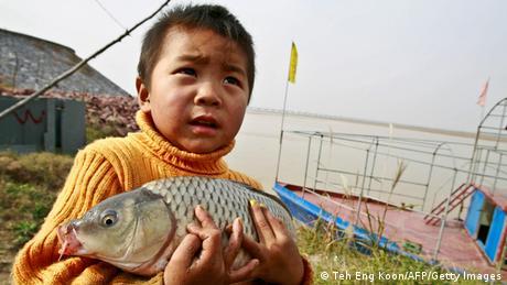 হোয়াংহো নদীর তীরে মাছ হাতে একটি ছেলে