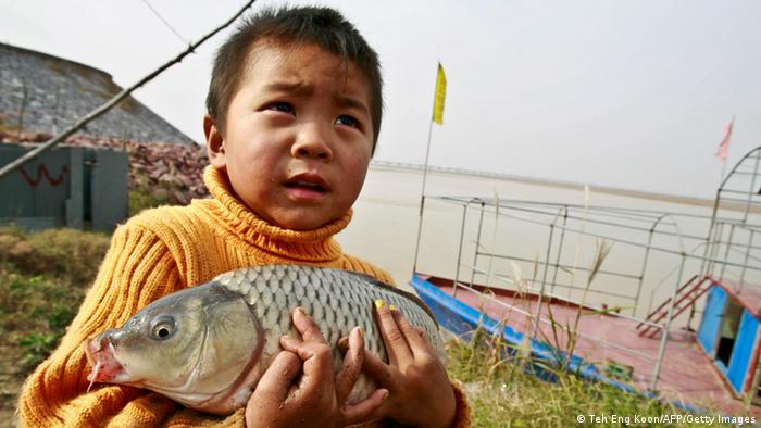 Yellow River, China: young boy holding dead fish