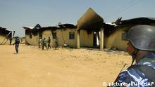 In this photo taken on Monday, Oct. 28, 2013, police and soldiers stand in front of a burnt out army barracks following an attack by Boko Haram in in Damaturu, Nigeria. Nigerian military and hospital reports indicate a 5-hour-long battle between Islamic extremists and troops in the capital of Nigeria¿s Yobe state last Thursday and Friday killed at least 90 militants, 23 soldiers and eight police officers. (AP Photo)