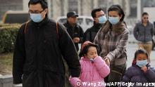 Family members wear face masks as they walk in strong winds near Tiananmen Square in Beijing on March 9, 2013. Strong winds and dust storms swept the Chinese capital on March 9. AFP PHOTO / WANG ZHAO (Photo credit should read WANG ZHAO/AFP/Getty Images)
