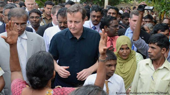 British Prime Minister David Cameron (C) visits at The Sabapathi Pillay Welfare Centre in Jaffna, some 400 kilometres (250 miles) north of Colombo on November 15, 2013. Britain's Prime Minister David Cameron made an historic visit to Sri Lanka's former warzone, stealing the spotlight from a Commonwealth summit after the host, President Mahinda Rajapakse, warned against passing judgement on his country's past. AFP PHOTO/ LAKRUWAN WANNIARACHCHI (Photo credit should read LAKRUWAN WANNIARACHCHI/AFP/Getty Images)