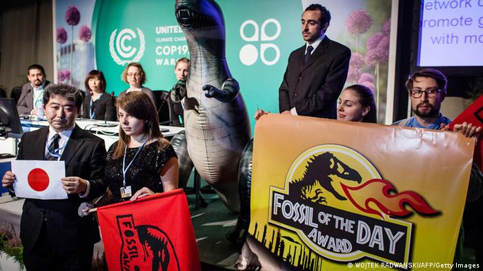 An Action Network (CAN) activist is seen during CAN press conferance at United Nations Climate Change COP19 as she announces that Fossil of the Day Award goes to Japan in reaction after Japan decision to slashing its goal for reducing climate-altering carbon emissions during CAN press conferance at United Nations Climate Change COP19, on November 15, 2013 in Warsaw. (Photo credit should read WOJTEK RADWANSKI/AFP/Getty Images)