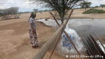 Woman observed water flowing from pipe into pool (Photo: UNESCO)