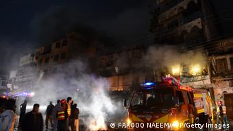 Pakistani rescuers and security personnel gather in front of a burning market after sectarian clashes near a Sunni mosque during the Shiite Muslim procession (Photo: FAROOQ NAEEM/AFP/Getty Images)