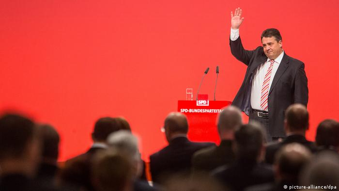 German politician Sigmar Gabriel raises his hand at a podium before a red backdrop. Photo: Hannibal