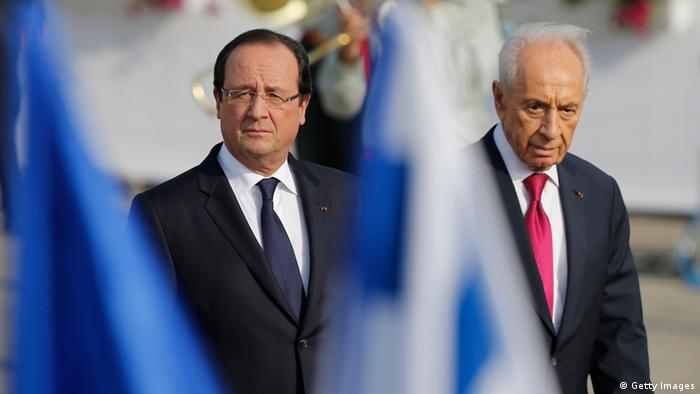 French President Francois Hollande (C) walks alongside his Israeli counterpart Shimon Peres (R) upon his arrival at Ben Gurion International Airport on November 17, 2013 in Tel Aviv. Hollande landed at Israel's Ben Gurion airport for a three-day visit likely to be dominated by the Iranian nuclear issue, an AFP correspondent said. AFP PHOTO / MARCO LONGARI (Photo credit should read MARCO LONGARI/AFP/Getty Images)