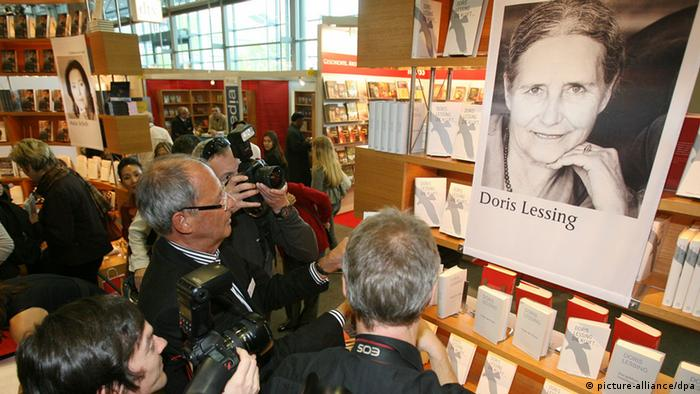 Journalists photograph and surround a book display with a picture of Doris Lessing Photo: Boris Roessler