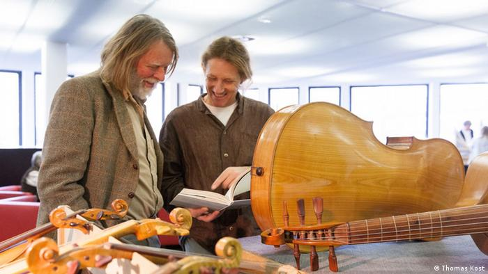 Two men having a discussion behind several instruments (c) Thomas Kost
