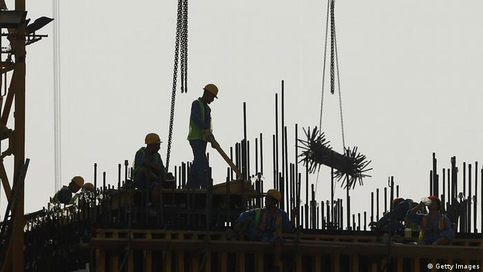 The silhouette of construction workers in Doha, Qatar