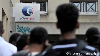 Unemployed people queue by a National Agency for Employment in Paris