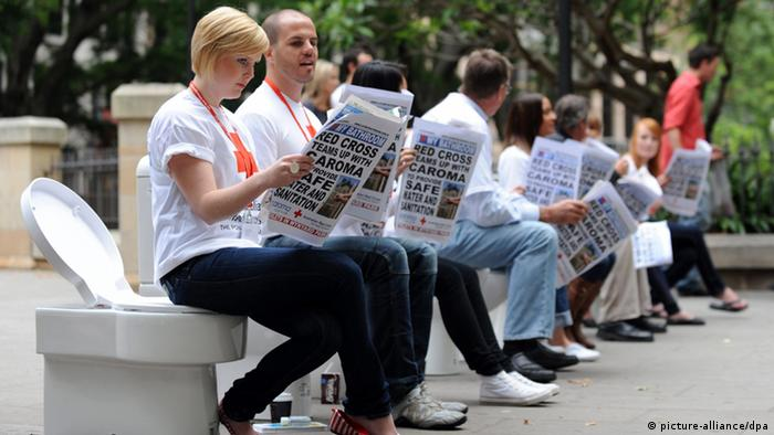 Activists sit on toilets for a promotional event for World Toilet Day (EPA/DEAN LEWINS)