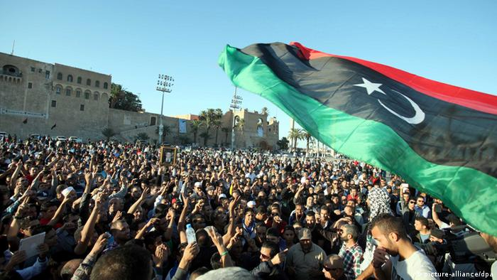epa03953033 Libyans wave the national flag and shout slogans as they attend the funeral of protesters killed during a demonstration in Tripoli, Libya, 16 November 2013. At least 27 people were killed and more than 235 injured when gunmen opened fire on 15 Novembe, in Tripoli on protesters who were demanding an end to the presence of armed militias in the Libyan capital. EPA/SABRI ELMHEDWI