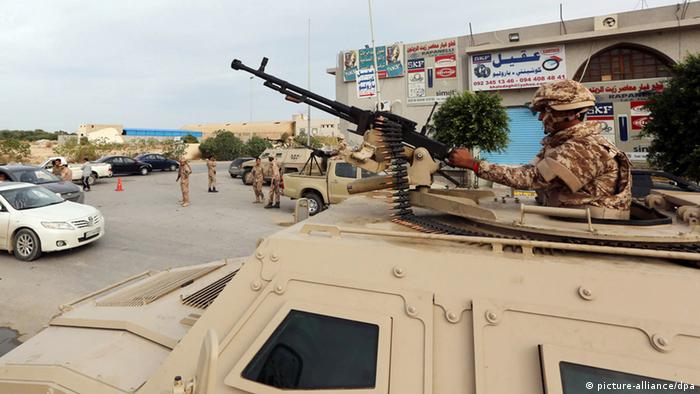 Libyan soldiers, one on an armoured personnel carrier 