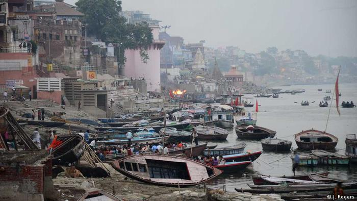Funeral pyres burn as boats lie tethered on the banks of the Ganges river in Varanasi (Photo: Janak Rogers)