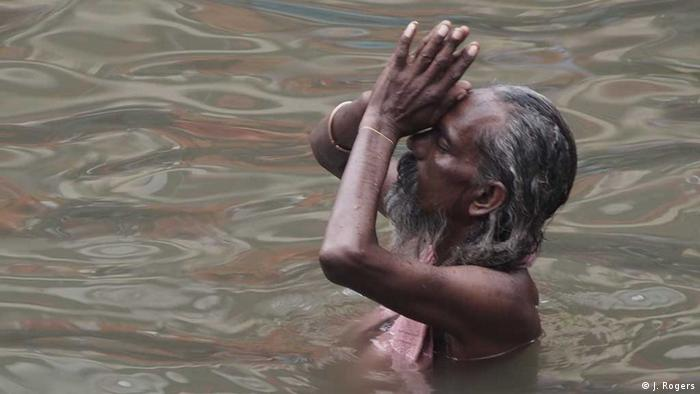A Hindu ascetic or sadhu praying in the Ganges river in Varanasi, India (Photo: Janak Rogers)