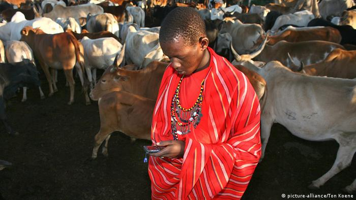 A young Massai guarding his herd and using a cell phone
