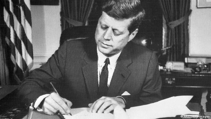 US President John Fitzgerald Kennedy signs the order of naval blockade of Cuba, on October 24, 1962 in White House, Washington DC, during the Cuban missiles crisis. On October 22, 1962, President Kennedy informed the American people of the presence of missile sites in Cuba. Tensions mounted, and the world wondered if there could be a peaceful resolution to the crisis, until November 20, 1962, when Russian bombers left Cuba, and Kennedy lifted the naval blockade. (Photo credit should read /AFP/Getty Images)
