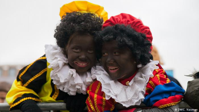 Two young caucasian children wear blackface make-up and brightly colored jester costumes. Photo: Carl Nasman