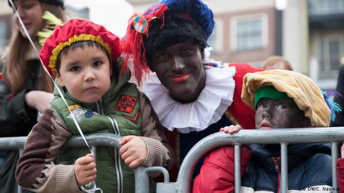 A man in blackface and wearing jester costume leans next to a young child - also wearing a jester costume - for a picture.