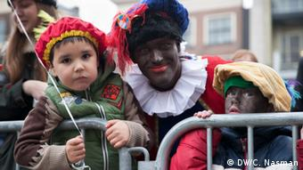 Black Pete and two Dutch children on the Sinterklaas parade in Amsterdam, Photo: DW/C. Nasman