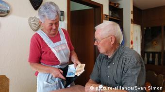 Ältere Frau zeigt einem älteren Mann Geldscheine