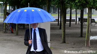 Ilustracija: muškarac s kravatom pod kišobranom s bojama EU zastave