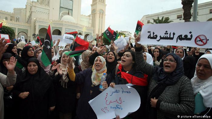 Libyan protesters wave their national flag nd banner reading in Arabic 'yes to police' (EPA/SABRI ELMHEDWI)