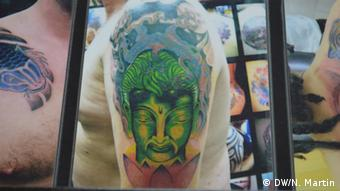 Description: An example of a Buddha tattoo on a man's arm Date: 11/11/13 (Photo: Nik Martin)