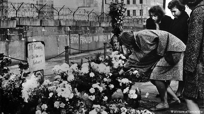 People laying flowers at the Berlin Wall