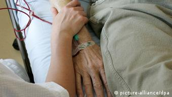 A woman holds the arm of an old man wishing to die in the hospital to support him