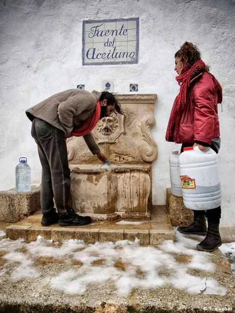 A brown stone fountain on a gray stone wall is reached into by a man while a woman stands nearby, waiting. Photo: Thomas Wagner