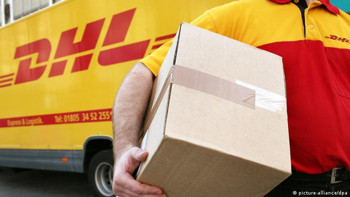 Сотрудник DHL несет пакет на фоне машины с логотипом компании