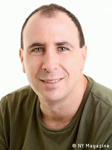 Wearing a green shirt, Jonathan Chait smiles at the camera in a professional photograph.
