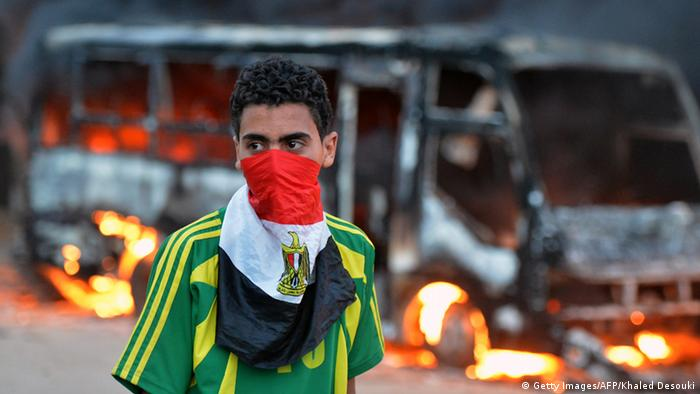 An Egyptian protester stands in front of burning bus belonging to Muslim brotherhoods supporters during clashes near the movements' headquarters in Cairo on March 22, 2013. Gunshots were heard as hundreds of opposition activists and the Islamists battled in the streets of the Mokattam neighbourhood where the headquarters are situated. AFP PHOTO/KHALED DESOUKI (Photo credit should read KHALED DESOUKI/AFP/Getty Images)