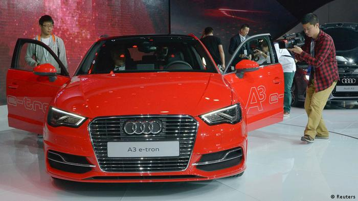 Visitors film an Audi A3 e-tron car at the Guangzhou International Automobile Exhibition in Guangzhou, Guangdong province, November 21, 2013. Luxury car dealers are resorting to offering customers massages, mini-golf and other gimmicks, hoping this will give them an edge in a ferociously competitive Chinese market where brand loyalty is less common than in the West. Audi will open its Innovation Exhibition at the Guangzhou auto show on Thursday, showcasing its technologies and concept cars such as the Crosslane Coupe, as well as the new generation Audi 3, including the plug-in hybrid A3 Sportback e-tron. REUTERS/Stringer (CHINA - Tags: TRANSPORT BUSINESS)
