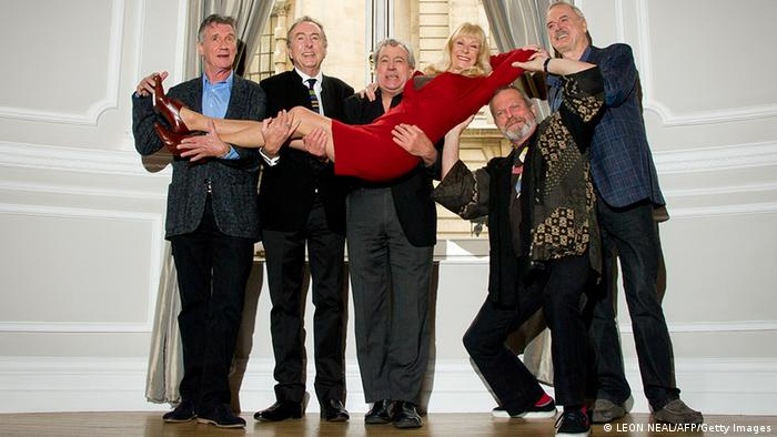 British comedy troupe Monty Python, (L-R) Michael Palin, Eric Idle, Terry Jones, Terry Gilliam and John Cleese hold up Python colaborator Carol Cleveland as they pose for a photograph during a media event in central London on November 21, 2013. Cue endless jokes about resting parrots -- the five surviving members of Monty Python, Britain's cult comedy troupe, announced on November 21 they will take to the stage again next year, three decades after their last performance together. Photo: AFP/Getty