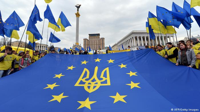 Activists of Ukrainian movement 'For European Future' hold EU flag with the Ukraine national emblem during their rally at Independence Square in Kiev on October 30, 2013. They have launched a campaign for a referendum in support of the European choice of Ukraine and against the country's joining to the Customs Union with Russia. AFP PHOTO/ SERGEI SUPINSKY (Photo credit should read SERGEI SUPINSKY/AFP/Getty Images)
