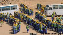 epa03956764 Foreign construction workers queue up for the bus back to their accommodation camp in Doha, Qatar, 19 November 2013. The previous day, football's ruling body FIFA said it will continue to put pressure on 2022 World Cup hosts Qatar over the conditions of migrant workers in the country's construction sector, but issued no deadline for improvement. Britain-based rights group Amnesty International said 17 November that workers in the oil- and gas-rich Gulf state suffered difficulties including 'non-payment of wages, harsh and dangerous working conditions, and shocking standards of accommodation.' EPA/STR