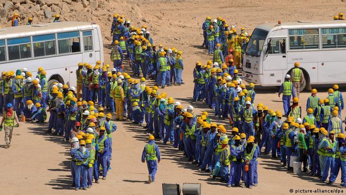 Katar Ausländische Bauarbeiter warten auf ihren Bus zurück zur Unterkunft in Doha (picture-alliance/dpa)