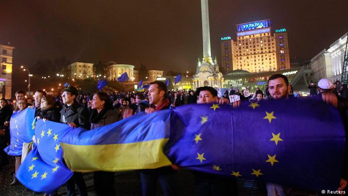 Demonstrators hold Ukrainian and European Union flags during a rally in Kyiv in November 2013 (Reuters)