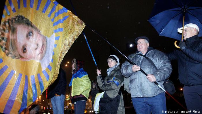 Activists hold a flag with the image of former Ukrainian Prime Minister Yulia Tymoshenko during a night rally in support of Ukraine's integration with the European Union in the center of Kiev, Ukraine, Friday, Nov. 22, 2013. Ukraine's president-controlled parliament on Thursday failed to pass any of a flurry of proposed bills allowing the release of jailed former premier Yulia Tymoshneko, dealing a harsh blow to this ex-Soviet republic's chances of integration with the European Union. Photo: AP