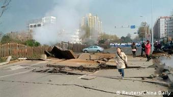A woman runs on a damaged street after a pipeline explosion in Huangdao, Qingdao, Shandong Province November 22, 2013. According to Xinhua News Agency, the pipeline blast occurred early Friday morning which resulted in an oil leakage, killed at least six people and left seven severely injured. REUTERS/China Daily (CHINA - Tags: DISASTER ENERGY TPX IMAGES OF THE DAY) CHINA OUT. NO COMMERCIAL OR EDITORIAL SALES IN CHINA